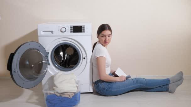 Verärgerte Frau sitzt auf dem Boden neben Waschmaschine im Zimmer