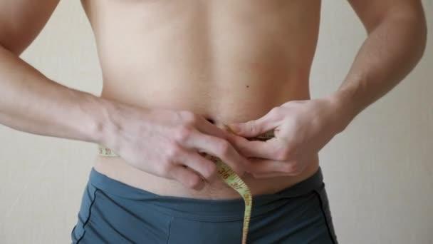 mladý muž prohmatává břicho a boky a provádí měření pomocí centimetrové pásky