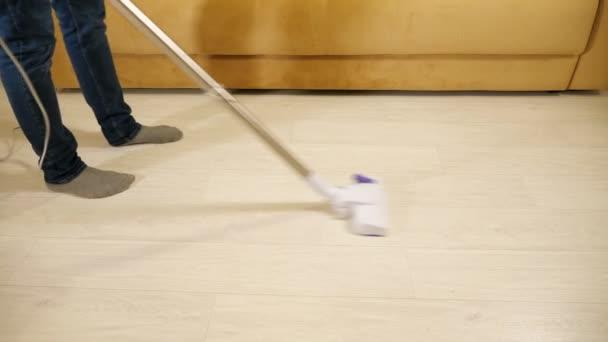 Nerozpoznatelný muž vysává podlahu s drátovým vysavačem.