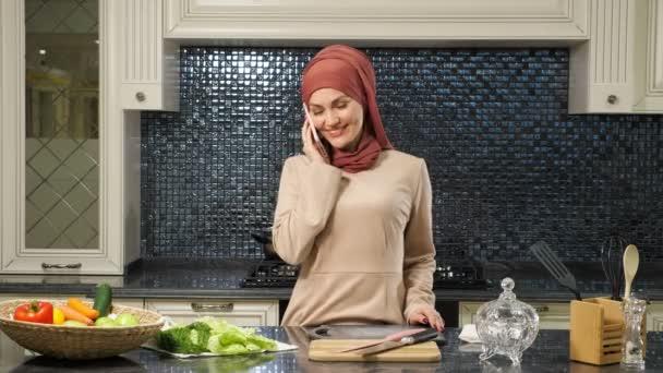 žena v hidžábu mluví na smartphone stojící u kuchyňského stolu