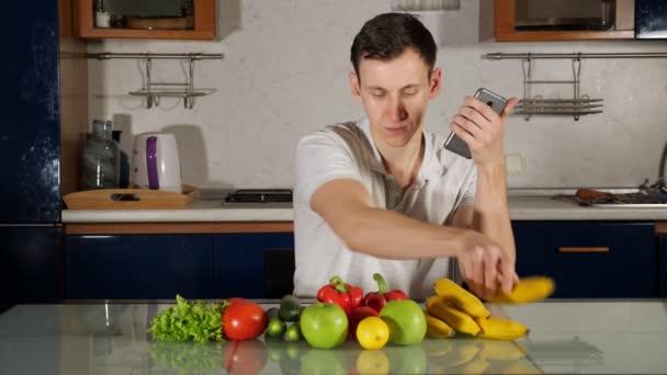 Muž hledá recept na salát sedí v blízkosti čerstvé zeleniny