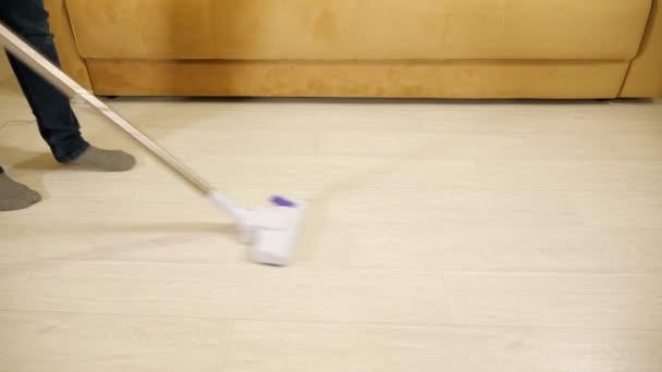 Úklid domu. Muž vysává podlahu s drátovým vysavačem