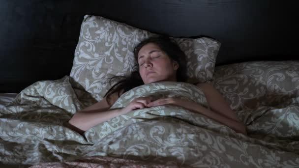 Az alvó nőnek rémálma van.