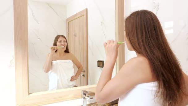 mladá žena kartáče zuby s bílým zubním kartáčkem detailní up