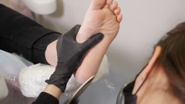 Junge Pediküre-Meisterin behandelt Füße mit Feile