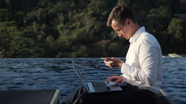 man works on laptop looking in phone against forest and pool