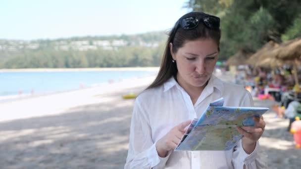 Mladá žena v bílé košili na pláži považuje mapu