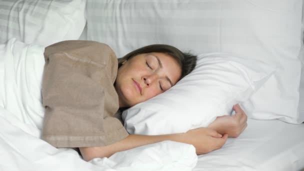 šťastná žena spí v posteli s dekou a polštáři v hotelu