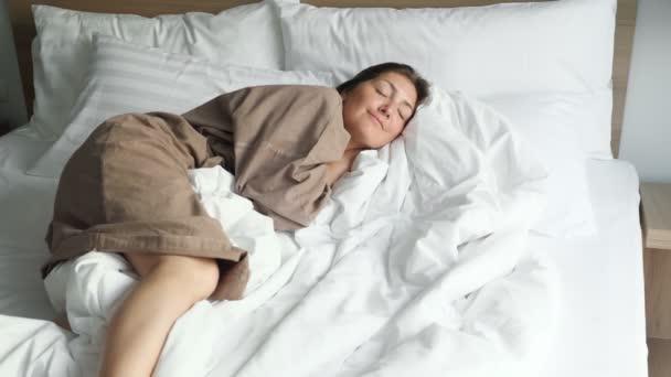 žena v županu spočívá na měkké posteli s přikrývkou a polštáři