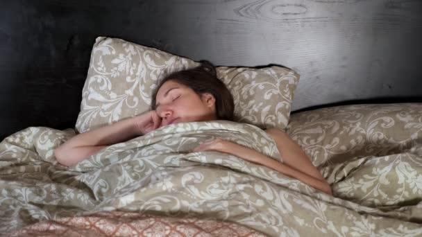 Mladá žena spí v ložnici