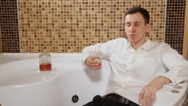 opilý muž v kalhotách a košili leží ve vaně a pije alkohol