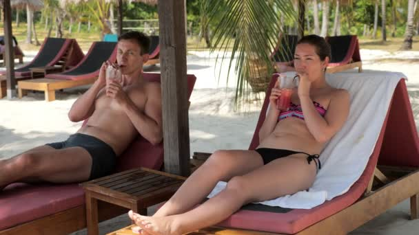 young couple rest on sunbeds and drink a cocktail