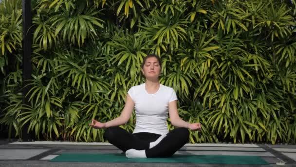Meditation an der frischen Luft. Frau in weißem T-Shirt in Lotusposition