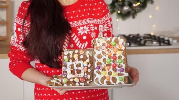 žena drží perník dům proti vánoční dekorace