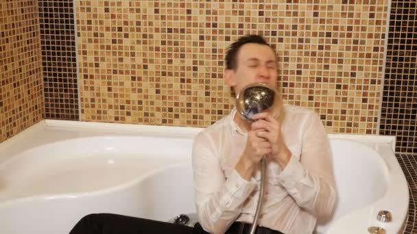 muž v košili a kalhotách ve vaně s vodou zpívá