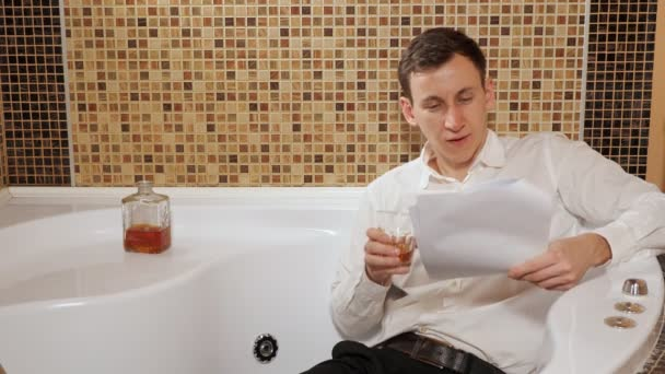 opilý muž v kalhotách a košili leží ve vaně a studuje dokumenty
