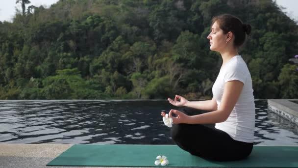 mladá žena sedí v lotosové poloze v blízkosti střešního bazénu