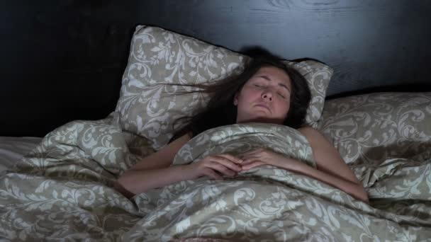 A fiatal nőnek rémálma van. Nyugtalan és nyugtalan alvás
