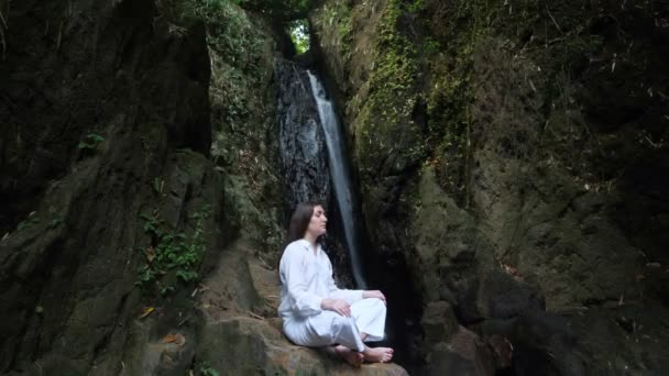 woman meditates in lotus position on rock against waterfall