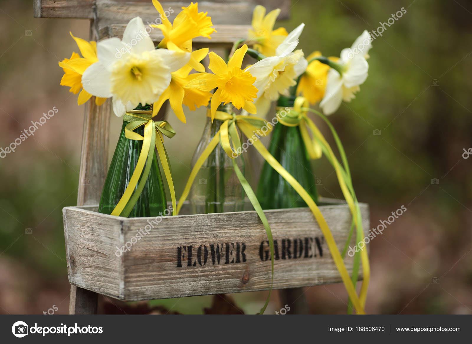 Fruhlingsblumen In Grunen Flaschen Im Garten Oster Deko Stockfoto