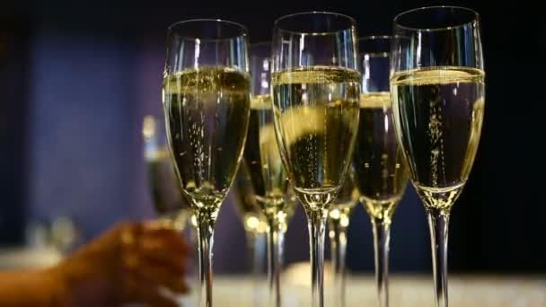 A csapos poharakat szolgál fel a bárban egy pohár pezsgő hátterében. A vendégek elviszik a poharakat.