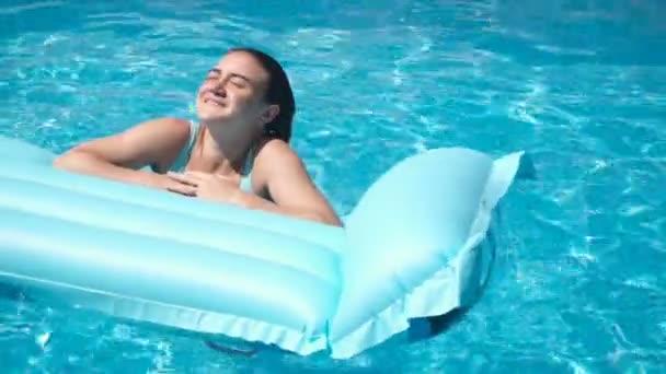 Ein junges hübsches Mädchen liegt auf einer Matratze im Pool und sonnt sich in der Sonne