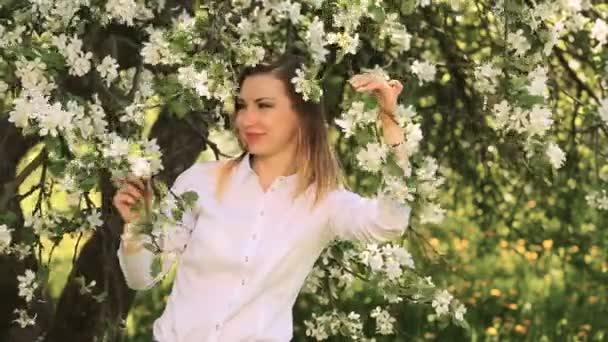 A pretty young girl among blossoming Apple trees in the Apple orchard