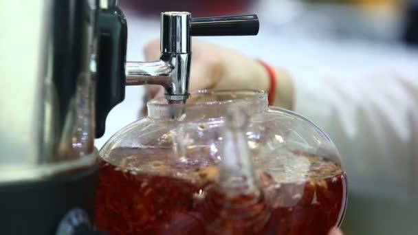 A tea sommelier forró vizet önt egy átlátszó teáskanna pohárba.