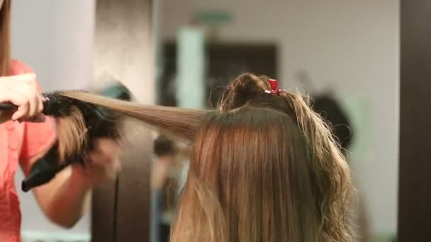 Styling the hair of a young pretty woman with a Hairdryer in a beauty salon