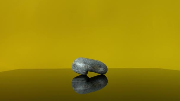 Close-up of stone on black desk of glass, background of yellow color with reflection.