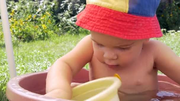 Niedliche kleine Kind Baden und Trinkwasser aus Spielzeug Eimer