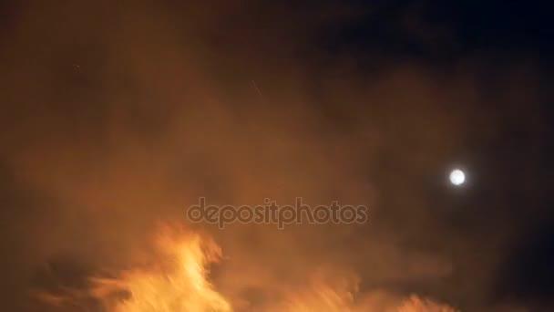 Hořící oheň. Noční obloha na pozadí s měsícem