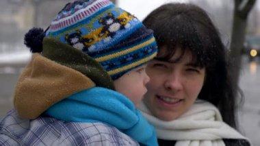 Mooie moeder neemt schattig kind handen kussen buiten tijdens
