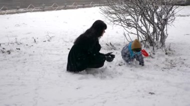 Young Beautiful Mother And Cute Child Play Outdoors During Snowfall. Winter City