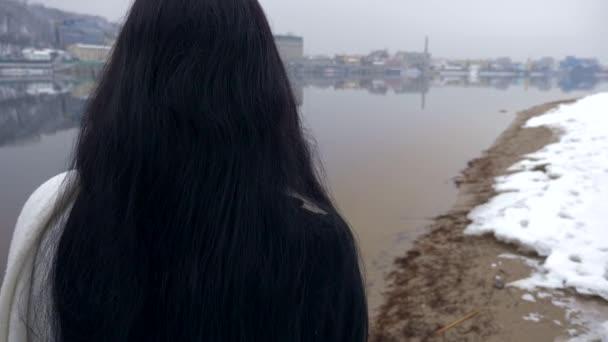 Krásná žena s smutné emoce chodí na břehu řeky myšlení. Zimní Zpomalený pohyb