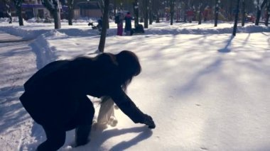 Pretty Brunette Girl Draws Heart On Snow. Sunny Day In Winter City Park. Slow Motion 30 fps 1/2 real time speed 60 fps