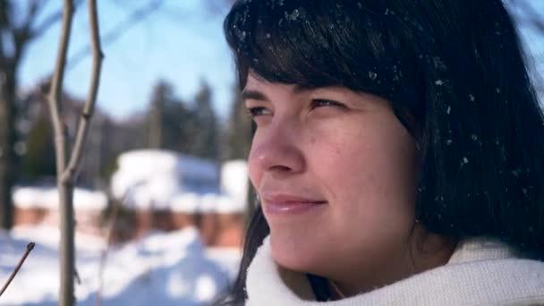 Közeli kép: csinos női arc. Hópelyhek a haj. Fiatal felnőtt hó borítja, Városliget süt a nap. Városi élet. Lassú mozgás 30 fps 1/2 valós idejű sebesség 60 fps