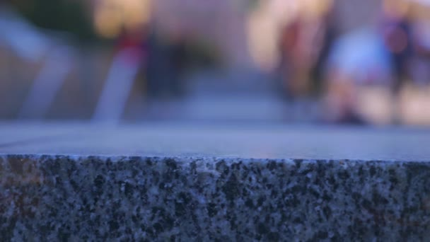 Close-up Polished Granite Stone Fence. Light Reflections Bokeh Abstract. People City Street