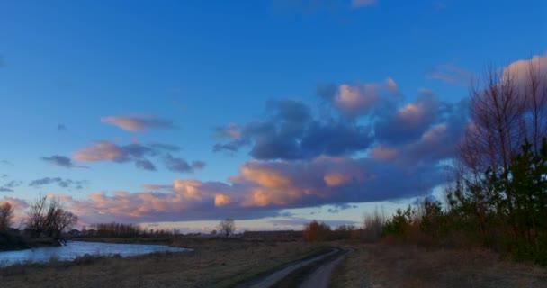 Večerní oblačnost Západ slunce nad řekou u Rural Road, Grove. Krajina Krajina Slunce svítí přes stromy. Dramatické mraky vanoucí větrem. Sezóna Změnit Podzim Zima Jaro Čas. Večerní oranžové modré nebe