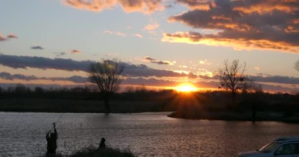 Muž Rybaření před západem slunce nad řekou. Rodina na dovolené Cestování autem. Pár odpočinku na přírodě. Večerní oblačnost nad krajinou Krajina. Dramatické mraky vanoucí větrem. Sezóna Změnit Podzim Zima Jaro Čas. Evening Red Orange Blue Sky
