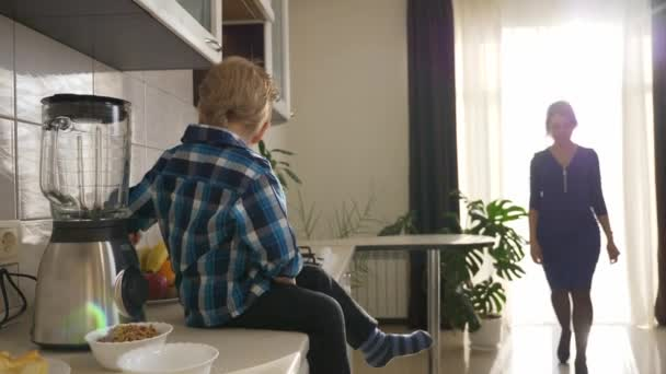 Rušná mladá matka připravuje rychlou snídani pro syna. Dítě sedí na kuchyňské lince. Ranní slunce svítí oknem. 2x Zpomalený pohyb, 0,5 rychlosti 60 FPS