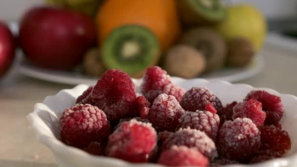 Close-up Frozen Raspberries on Kitchen Countertop. Morning Evening Sunshine through Window. 2x Slow motion, 0.5 speed 60 FPS