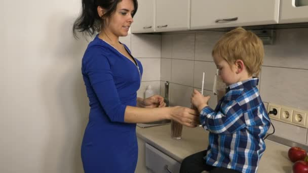 Mother Gives Fruit Cocktail to her Son. Young Woman and Child Enjoy Healthy Drink on Kitchen. Child Sitting on Kitchen Countertop. Morning Evening Sunshine through Window. 2x Slow motion, 0.5 speed 60 FPS