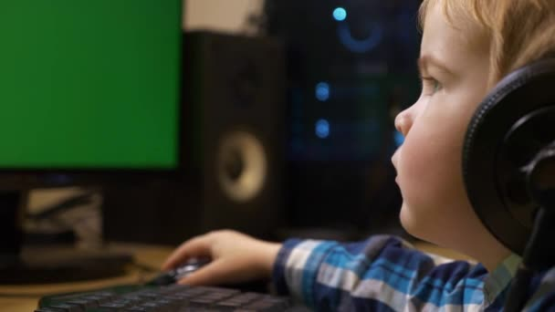 Little Child Surfing Internet Playing Watching Learning to Use Computer. Boy Sits in Front of Green Screen Monitors. Father's Editing PC Workstation. Gaming PC.