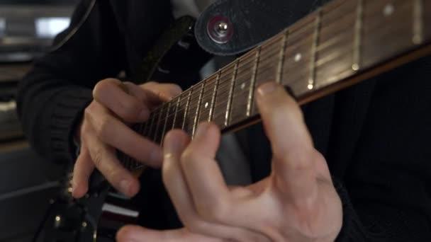 Ujjak a fogólapon. Közeli kezek zenét játszanak elektromos gitáron. Fiatal felnőtt zenész játszik és lemezek Music at Home Studio. 2x Lassú mozgás 0,5 sebesség 4K 60p