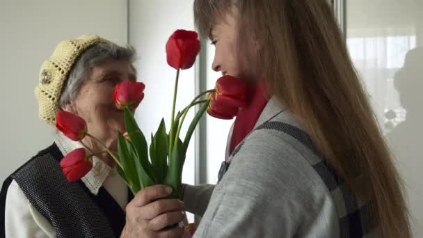 Mature Daughter Visits Elderly Mother Greets Hugs Gives Present and Tulip Flowers. Happy Senior Woman Birthday. 2x Slow motion 0.5 speed 60 fps