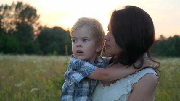 Šťastný milující matka objímání roztomilý malý syn. Rodina odpočívající na krásné přírodě. Sunset Sun Beams Flares. Večerní venkovská scéna. 2x Zpomalení - Poloviční rychlost 60 FPS