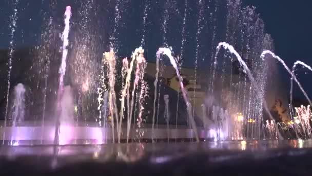 Fontána v noci downtown. Voda pak stoupá až opět to padá. V dolní části fontány světla svítí v různých barvách.