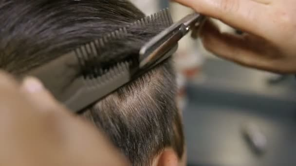 Man Hair Stylist is cutting short hair of a young man.