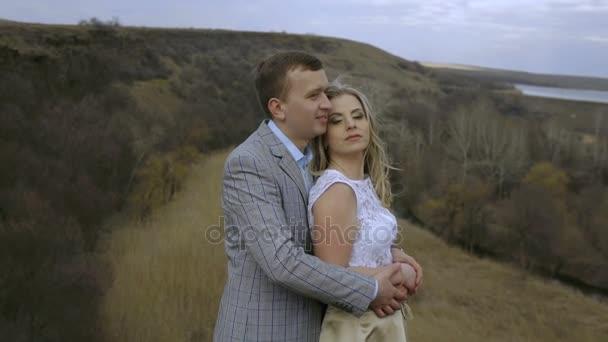 milující pár stojící v objetí na krásnou krajinu v poušti před západem slunce